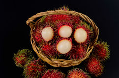 Rambutan in basket on black background. Rambutan in basket on a black background Royalty Free Stock Photos