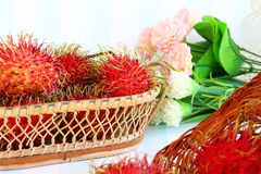 Rambutan in basket. On vintage style on retro background Stock Images