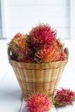 Rambutan. In basket on wood background stock photo
