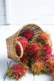 Rambutan. In basket on wood background Royalty Free Stock Image