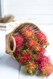 Rambutan. In basket on wood background stock photography