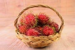 Rambutan in basket on wooden floors Stock Photography