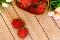 Rambutan in basket. On wooden floors Royalty Free Stock Images