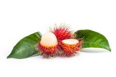 Rambutan e delizioso freschi con le foglie su fondo bianco Immagini Stock