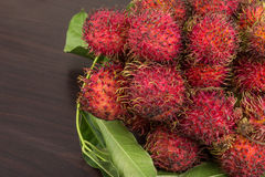 Rambutan. Fresh Rambutan with leaves on the wooden background Royalty Free Stock Photo