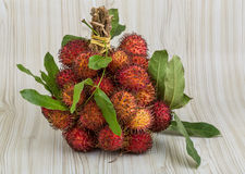 Rambutan. Fresh Rambutan with leaves on the wooden background Stock Images