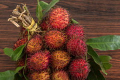 Rambutan. Fresh Rambutan with leaves on the wooden background Royalty Free Stock Image