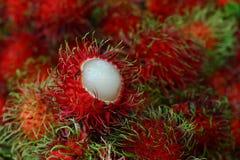 Rambutan, Frucht in der roten Farbe mit haarigem Heraus und weißes Innere lizenzfreie stockfotos