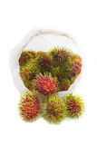 Rambutan-Frucht mit Plastiktasche auf weißem Hintergrund Lizenzfreie Stockfotografie