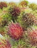 Rambutan-Frucht mit Plastiktasche auf weißem Hintergrund Lizenzfreies Stockfoto