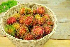 Rambutan fruit. Rambutan in basket on a wooden tabie Royalty Free Stock Photos