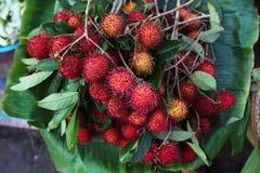 Rambutan fruit bunch on the fruit market in Asia. Rambutan fruit bunch on banana leaves selling on the fruit market in Asia Royalty Free Stock Images
