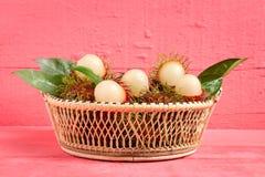 Rambutan fruit on wood color pink. in basket.  Royalty Free Stock Photo