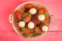 Rambutan fruit on wood color pink. in basket.  Stock Photography