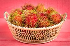 Rambutan fruit on wood color pink. in basket.  Royalty Free Stock Photography