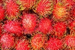 Rambutan fruits at local market. Closeup of fresh bunch of ripe and delicious Rambutan fruits at local market Stock Photos
