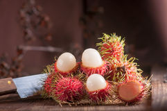 Rambutan and knife on wood table.  Stock Image