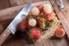 Rambutan and knife on wood table Royalty Free Stock Photo