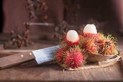 Rambutan and knife on wood table.  Stock Photo
