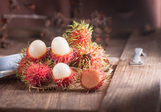 Rambutan and knife on wood table.  Royalty Free Stock Images
