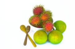 Rambutan på en vit bunke med orange frukt Fotografering för Bildbyråer