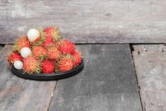 Rambutan sweet fruit fresh in plate on wood background. Rambutan sweet t fresh in plate on wood background :Select focus with shallow depth of field Stock Photography