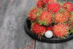 Rambutan sweet fruit fresh in plate on wood background. Rambutan sweet t fresh in plate on wood background :Select focus with shallow depth of field Royalty Free Stock Images