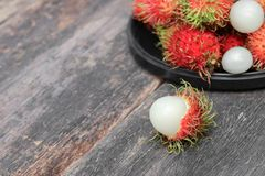 Rambutan sweet fruit fresh in plate on wood background. Rambutan sweet t fresh in plate on wood background :Select focus with shallow depth of field Royalty Free Stock Photos