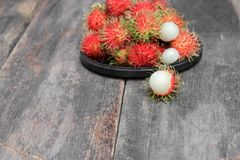Rambutan sweet fruit fresh in plate on wood background. Rambutan sweet t fresh in plate on wood background :Select focus with shallow depth of field Royalty Free Stock Photography