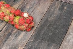 Rambutan sweet fruit fresh on wood background. Select focus with shallow depth of field Royalty Free Stock Photography