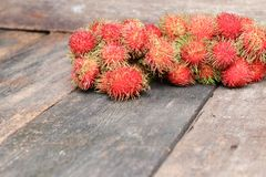 Rambutan sweet fruit fresh on wood background. Select focus with shallow depth of field Stock Photo