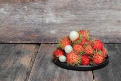 Rambutan sweet fruit fresh in plate on wood background. Rambutan sweet t fresh in plate on wood background :Select focus with shallow depth of field Royalty Free Stock Photo