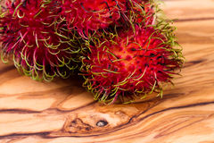 Rambutan a sweet tropical fruit. Close up of a group of rambutan on a wooden table Royalty Free Stock Images