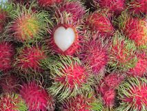 Rambutan is a tropical fruit, stacked together. Top results pier. Cing the heart-shaped to show the inside to eat Royalty Free Stock Photography