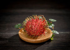 Rambutan with vanilla on wooden plate isolated on the black   background. Royalty Free Stock Image