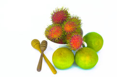 Rambutan on a white bowl with orange fruit. Stock Image