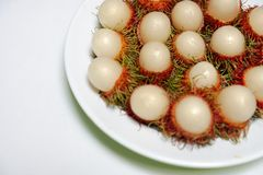 Rambutan in the white dish. On the table Stock Photography