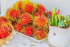 Rambutan on white table. Fresh Rambutan in bamboo basket on wooden table background Royalty Free Stock Photos