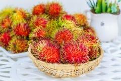 Rambutan on white table. Fresh Rambutan in bamboo basket on wooden table background Royalty Free Stock Image