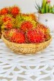 Rambutan on white table. Fresh Rambutan in bamboo basket on wooden table background Stock Images