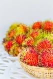 Rambutan on white table. Fresh Rambutan in bamboo basket on wooden table background Stock Photos