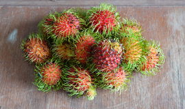 Rambutan on the wood background. Bunch of rambutan on the wood background Royalty Free Stock Images
