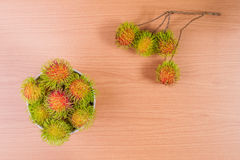 Rambutan on wood background. Fresh rambutan on wood background Royalty Free Stock Image