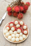 Rambutan. In wooden dish and knife on wood table Stock Images