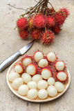 Rambutan. In wooden dish and knife on wood table Stock Photos
