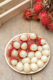Rambutan. In wooden dish on wood table Stock Photos
