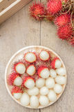 Rambutan. In wooden dish on wood table. Top view Royalty Free Stock Photo