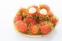 Rambutan in the wooden disk. On white background Stock Image