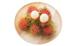 Rambutan in the wooden disk. On white background Stock Photos