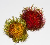 Rambutans. A pair of contrasting rambutans, the red one being the ripe, juicy one stock photos